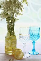 Slices of lemon and bouquet of wild flowers in carafe of water