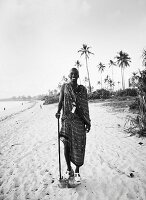 Black and white photo of African man wearing traditional clothing and sandals on beach