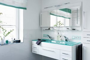 A trough-style washstand for two with a shimmering turquoise glass top built into a white unit with a multi-door, mirrored cabinet hanging above it in a modern bathroom with a window