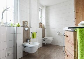 A white-tiled bathroom with a bidet and toilet against the window wall with light brown floor tiles that are also used as backing for the sanitary ware