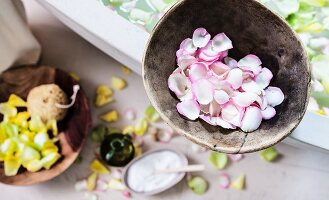 A bowl of rose petals on the edge of a bathtub filled with a scented petal bath