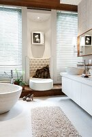 The perfect spa bathroom – a lounger upholstered in light, artificial leather with a semi-circular back decorated with buttons and a custom-made teak platform with storage drawers
