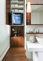 A teak platform and a tall cupboard with a minibar in front of a bathroom window; to the side a limestone wash basin and a narrow wall lamp in front of a mirror