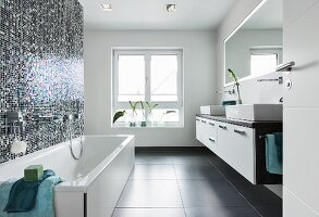 A shimmering, blue-and-white mosaic tiled wall behind a bathtub opposite a double washstand with a console basin and a wall-mounted, illuminated mirror