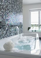 A shimmering mosaic tiled wall behind a bathtub with a bubble bath running