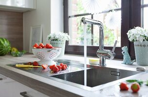 A square sink with the tap running and freshly washed strawberries in a white colander