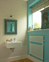 Mirror with ornate, Moroccan frame above modern sink; radiator-towel rack on turquoise wall to one side and antique cabinet on windowsill