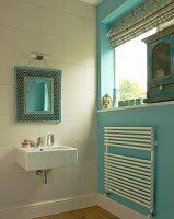 Spiegel mit marokkanischem Zierrahmen über modernem Waschbecken; türkisblaue Seitenwand mit Handtuch-Heizkörper und antikes Schränkchen auf Fensterbank
