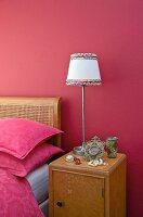 Nachtkästchen mit Lampe vor himbeerroter Wand, daneben Bettwäsche in Pink auf Jugendstil Bett mit Geflecht