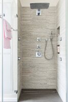 A floor-level, tiled shower with a rain head, a hand-held shower head and wall mounted jets