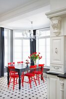 Black wooden table and red wooden chairs on black and white tiled floor in elegant window bay