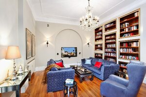 Blue sofa set and reading armchair with blue leather cover next to fitted shelving in traditional living room