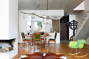 Dining area with traditional oak furniture, animal-skin rug, green classic chair and exposed concrete