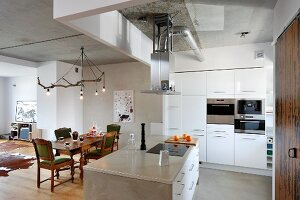 White, open-plan kitchen with free-standing island counter and ceiling lamp made from branch above traditional dining set