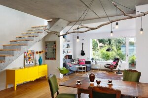 Lights hanging from large branch above oak table and upholstered chairs in open-plan interior; yellow sideboard below exposed concrete staircase