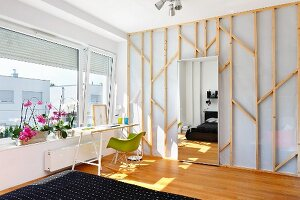 Sunny workspace with Eames Plastic Armchair below window in bedroom with mirrored door leading to dressing room
