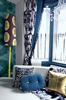 Various scatter cushions in bay window with draped curtains and standard lamp against patterned wallpaper
