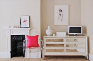 Pink cushion on Ghost chair in front of traditional fireplace next to elegant chest of drawers with mirrored fronts in niche