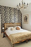Double bed with gilt, antique wooden frame against wall with black and white floral wallpaper