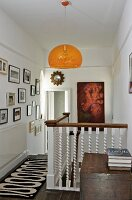 Orange pendant lamp above head of staircase on landing with white, wooden balustrade and gallery of pictures on wall