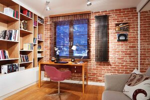 Simple workspace below window; pink swivel chair and wooden desk against brick wall, wooden, fitted shelving with painted fronts to one side