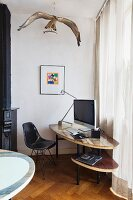 Black, classic-style shell chair at DIY computer desk below stuffed osprey