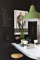 Pendant lamp with green metal lampshade above breakfast bar against wall painted with black chalkboard paint