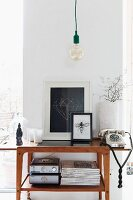 Minimalist, vintage pendant lamp above vintage telephone next to framed pictures on fifties-style console table against narrow section of wall