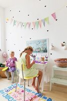 Two girls in bedroom with heart shaped stickers and bunting on wall