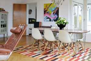 Retro dining area with woven, geometric rug and modern artwork on wall in background; leather armchair to one side
