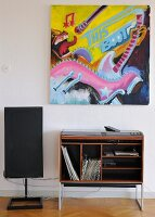 Modern painting above retro hifi cabinet with records in shelf compartment