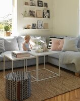 Toddler sitting on grey sofa in comfortable living room with books on floating shelves
