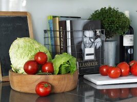 Books in wire basket on granite worksurface and wooden bowl of vegetables in front of vintage slate chalkboard