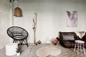 Pouffe and wicker chair in corner, floor cushions and leather couch on rug in loft-style interior
