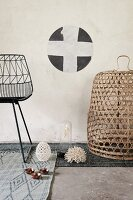 Detail of black metal chair and basket on various grey rugs below stencilled motif on wall
