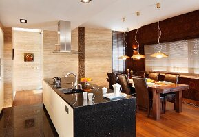 Free-standing kitchen counter clad in black stone and tasteful dining area with leather-covered chairs below modern pendant lamps