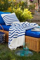 A wicker lounger with a blue cushion in a garden with a stripped throw and a cushion