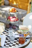 Fruit on a vintage stand, cafe au lait and honey on a breakfast table in a garden