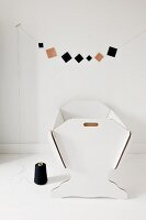Garland of paper squares above white, cardboard dolls' crib