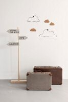 Playroom decorations; suitcases, signpost and hand-crafted clouds made from wire and cardboard on wall