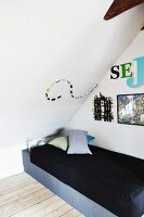 Single bed under sloping ceiling with creative arrangement of ornaments and decorative lettering on walls
