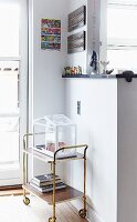Retro serving trolley against half-height partition decorated with colourful figurines