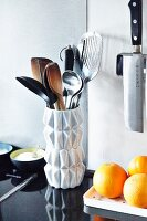 Wooden spoons and utensils in white, retro vase on black granite kitchen worksurface
