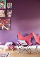 Butterfly chairs with dusky pink seats in front of purple-painted wall