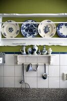 Kitchen utensils on small bracket shelf on tiled wall below carved shelf holding white and blue painted plates