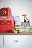 Set of children's suitcases, wooden duck on boxes and child's shoes on chest of drawers