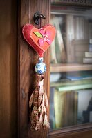 Key pendant with heart-shaped cushions and ribbon tassel hanging from key of glass-fronted cabinet