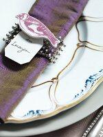 Rhinestone napkin ring with bird figurine and name card on napkin on plate