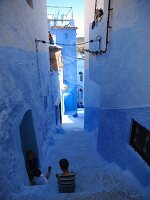 Children in a blue alleyway in the Medina of Chefchaouen, Morocco