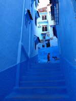Children playing in a blue alleyway in the Medina of Chefchaouen, Morocco